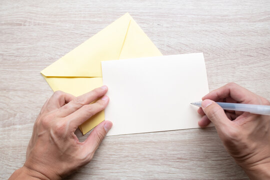 Male hands writing Empty cards on wooden table.