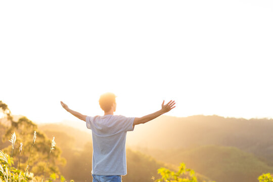 Happy young man with arms raised and sunset in the background