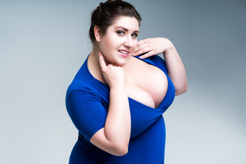 Happy plus size fashion model in blue dress with deep neckline, fat woman on gray background, body positive concept