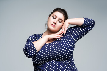 Plus size fashion model in blue polka dot dress, fat woman on gray background, body positive concept