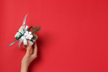 Woman holding giftbox of kraft paper with ribbons on red background. Greeting Xmas card. Boxing day. Top view