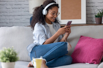 Beautiful young woman listening to music with headphones while using her smartphone sitting on sofa at home.