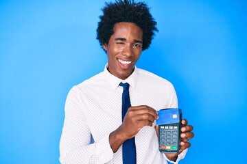 Handsome african american business man with afro hair holding dataphone and credit card winking looking at the camera with sexy expression, cheerful and happy face.