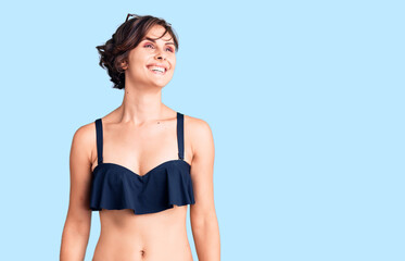 Beautiful young woman with short hair wearing bikini looking away to side with smile on face,...