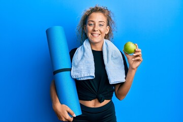 Beautiful caucasian teenager girl holding yoga mat and green apple smiling with a happy and cool...