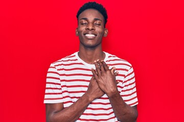 Young african american man wearing casual clothes smiling with hands on chest with closed eyes and grateful gesture on face. health concept.
