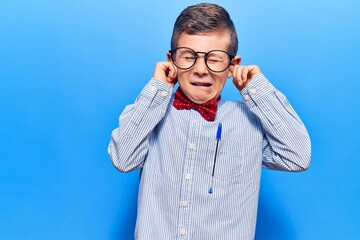 Cute blond kid wearing nerd bow tie and glasses covering ears with fingers with annoyed expression for the noise of loud music. deaf concept. Fotobehang