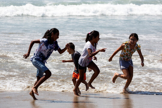 Children play in the water on the record heat wave, at Venice Beach in Los Angeles
