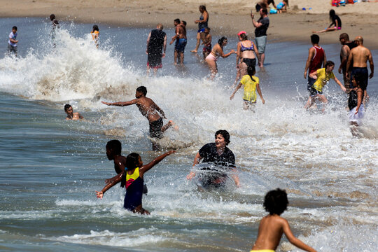 People play in the water on the record heat wave at Venice Beach in Los Angeles
