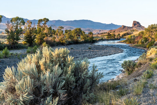 Rock outcropping over the river with trees and shrub on the banks and mountain in the background, South Fork Shoshone River, Cody, Wyoming
