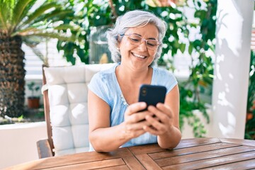 Middle age woman with grey hair smiling happy relaxing sitting at the terrace at home using...