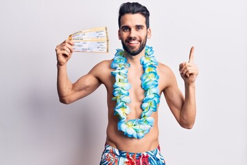 Young handsome man with beard wearing swimwear and hawaiian lei holding boarding pass smiling happy pointing with hand and finger to the side