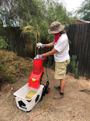 Adult male wearing thick protective gloves feeds garden sticks and small branches into an electric wood chipper.
