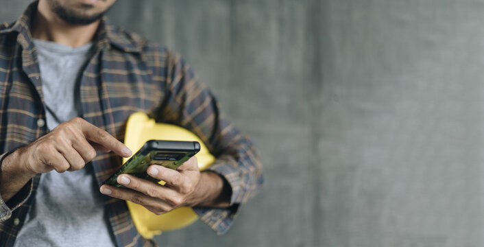 construction worker hands using smartphone on cement wall background with copy space