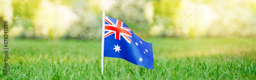 Australian flag standing on green grass. Australia day national holiday celebration. Nature country citizenship background outdoors. Web banner header.
