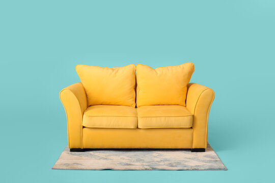 Stylish sofa and carpet on color background