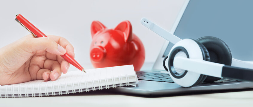 Savings. Laptop with headphones on white desk red coins bank and hand writing Distant learning or working from home, online courses, home finance concept. small business support or loans