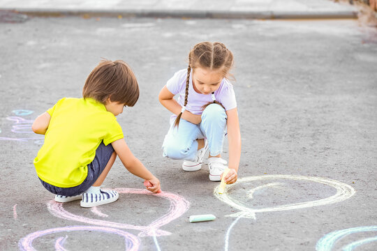 Little children drawing with chalk on asphalt