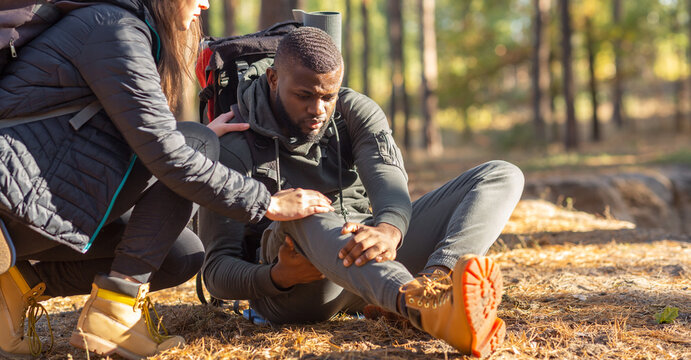 Unrecognizable woman comforting injured black guy, backpacking together by forest