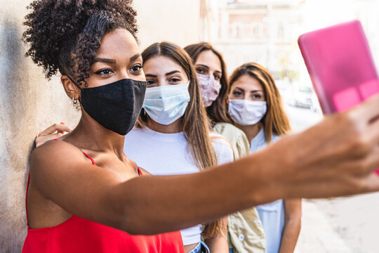 Four young multiracial friends women with face mask for protection by infection from Coronavirus, Covid-19 - Millennials taking a selfie with smartphone.