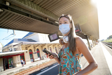 Young woman waiting for train on railway platform, wearing face mask