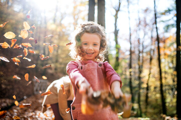 Small girl with mother on a walk in autumn forest, throwing leaves.
