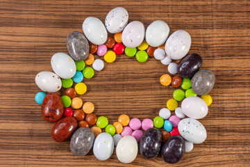 Colored eggs and colored chocolate tablets on exotic natural wood background