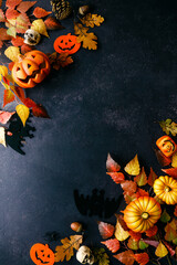 Pumpkins with Halloween decorations on dark background
