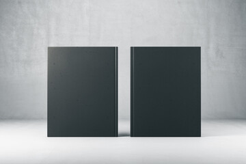 Two closed black hardcover book on gray background.
