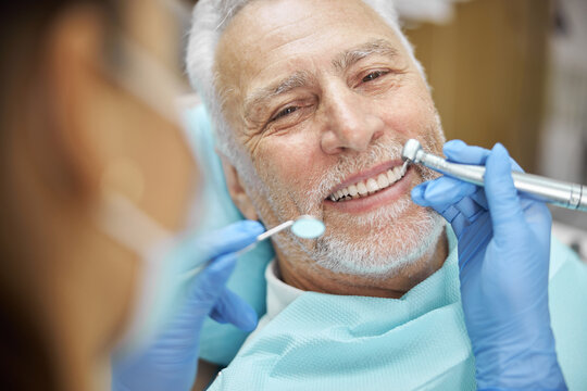 Mirthful senior citizen smiling during a dental treatment
