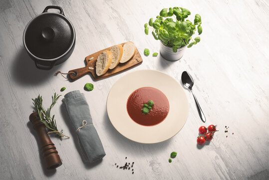 Bowl of fresh hot tomato soup on a whitewashed wooden counter. Fresh sliced bread, basil, cherry tomatoes and pepper kernels surround the bowl, accompanied by the black pot, napkin and pepper grinder.