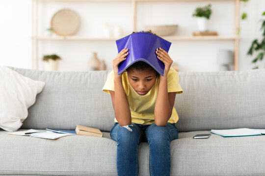 Upset Girl Covering Head With Exercise-Book Sitting On Sofa Indoors