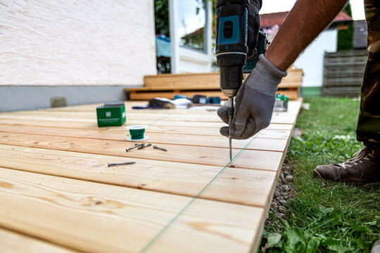 Building site - laying larch floorboards on a terrace. Installing of siberian larch flooring.