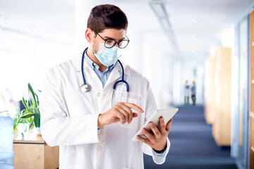 Portrait shot of male doctor wearing face mask while working on digital tablet