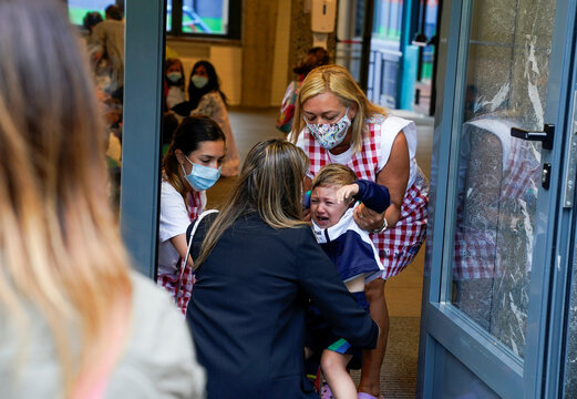 A teacher wearing a protective mask welcomes a pupil on the first day of school after summer holidays during the coronavirus disease (COVID 19) outbreak, at Colegio Pureza de Maria school in Bilbao