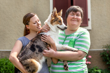 mental disabled woman in front of a house is holding her dog