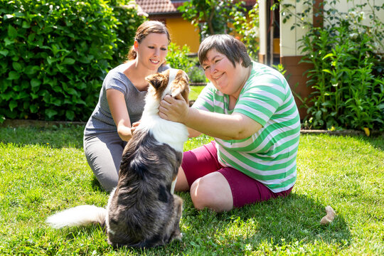 mentally disabled woman with a second woman and a companion dog