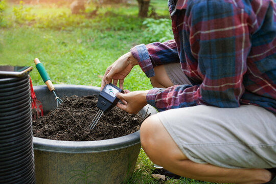 To measure soil pH, gardeners are using a monitor to measure pH balance, acidity, and alkalinity, use of modern agricultural tools. To prepare the soil to mix in vegetable gardening