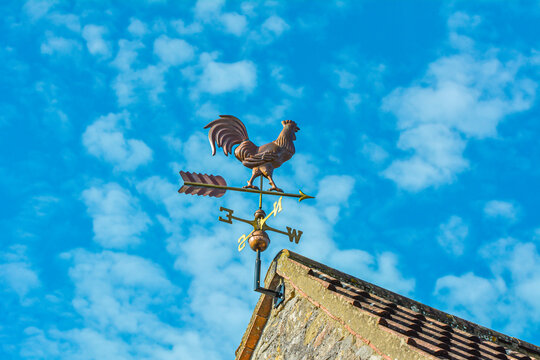 Copper cockerel, rooster or chicken weather vane on a farm with blue sky background