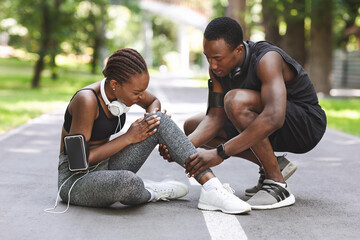 Sport Injury. Woman Suffering From Knee Trauma While Jogging With Boyfriend Outdoors