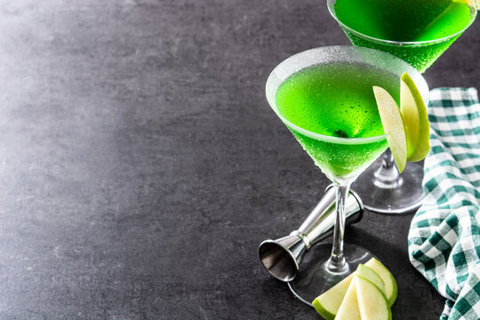 Green appletini cocktail in glass on black background. Copy space