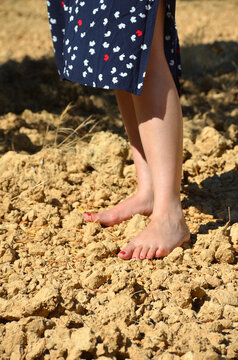 Young Woman Standing Barefoot on a Field