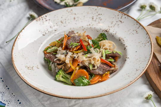 Chinese food beef noodles with broccoli, carrot, pepper and sesame seeds on the table
