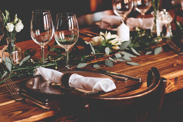 Wedding banquet, serving wooden table with silver plates and decorated with flowers