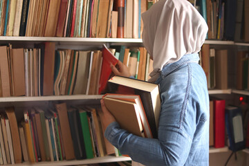 Asian muslim woman wearing hijab picking book in bookshelf, education concept, reading learning...