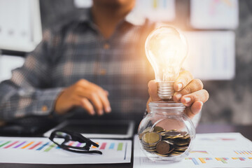 Innovation and creative business, businessman holding light bulb on glass of coins with financial...