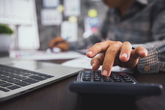 Close up hand of business man press on calculator, accounting and checking on financial graph paper and laptop to calculate profit and budget and income, accountant and counting concept
