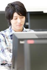Fototapeta PCを操作する男子大学生