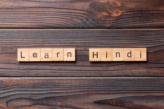 Learn Hindi word written on wood block. Learn Hindi text on table, concept