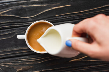 cropped view of barista adding milk to coffee in cup on wooden surface